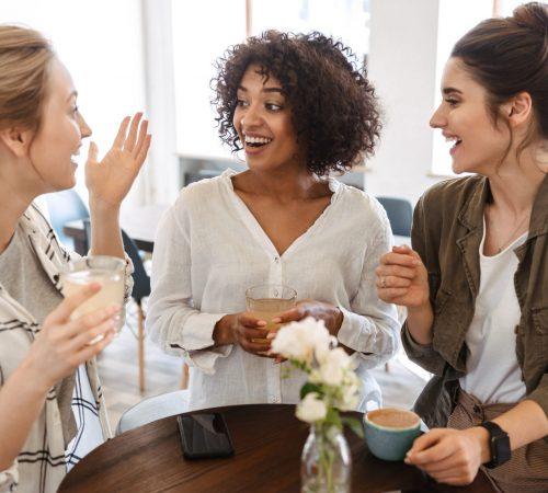 Happy young women friends having coffee break